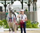 Liza Wilson stepped up at the 2015 North American Junior and Young Rider Championships, acting as a groom, friend, and supporter for friend, Alexandra Meghji and her mount, Iliado II. Photo courtesy of Diana Belevsky