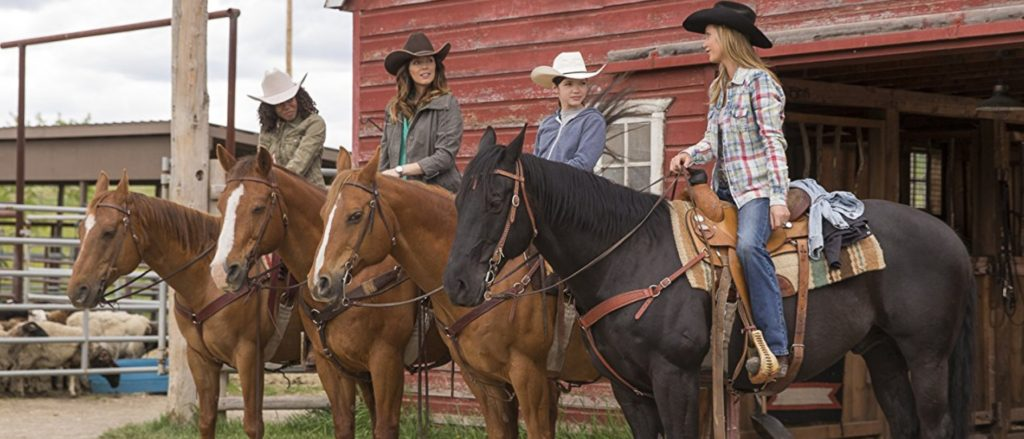 Michelle Morgan as Lou Fleming with other riders on CBC Heartland
