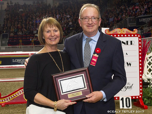 """John """"JT"""" Taylor was presented with the 2017 JC Official of the Year Award by Pam Law, Chair of the EC Jumping Committee, at the Royal Horse Show on Nov. 4, 2017 in acknowledgment of his exceptional career as a top FEI Jumping Judge. Photo by Cealy Tetley"""