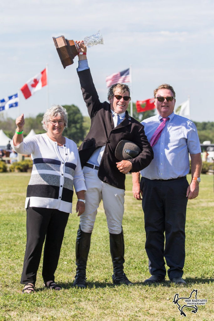 Hugh Graham, center, hoists the trophy following his win in the $132,000 CSI3* Ottawa International Grand Prix. Presenting on behalf of Wesley Clover Parks are Lady Ann Matthews and Chief Operating Officer, Tony Dunn.