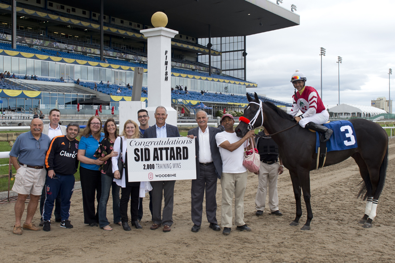 Woodbine's CEO and President Jim Lawson congratulates trainer Sid Attard, who is joined by family and friends in the winner's circle on July 22 to celebrate his 2,000th career win.