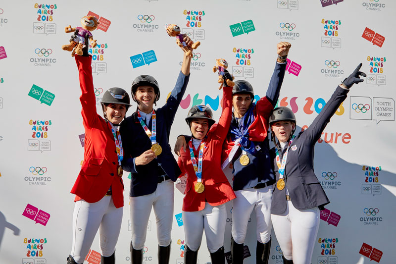 Team North America celebrate their historic victory as they clinched the Team Gold medal in a nail biting jump off to top the podium at the Youth Olympic Games Buenos Aires 2018. L to R: Nicole Meyer Robredo, Pedro Espinosa, Marissa del Pilar Thompson, Mateo Philippe Coles, Mattie Hatcher Team USA, Photo by FEI / Liz Gregg