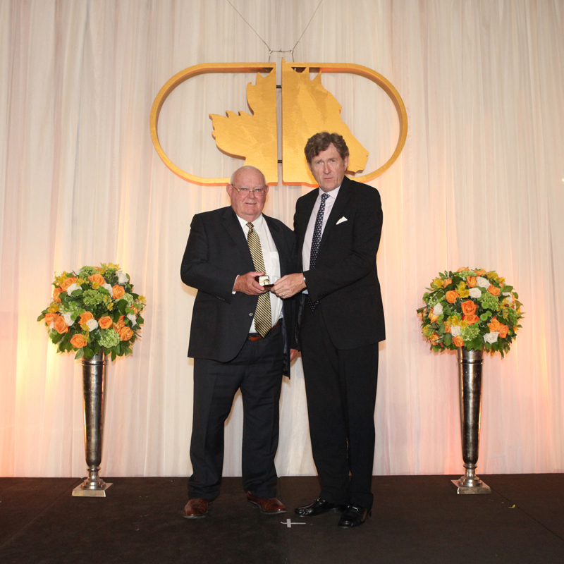 Bill Graham (left) receiving his Canadian Horse Racing Hall of Fame ring at the 2014 induction ceremony from trainer Mike Doyle. Photo courtesy Iron Horse Photo/Canadian Horse Racing Hall of Fame